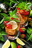 Mojito cocktail, iced drink with lime, strawberry and mint leaves