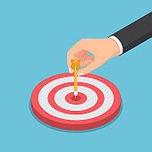 Isometric businessman hand putting dart arrow on center of the bullseye