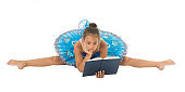 Girl ballerina stretching split while read book. Ballet career issues. Depriving children ballerina. Most of time child dancer spend gym training practicing stretching. No time for school studying