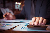 asian business man working with new startup project  pointing graph discussion and analysis data charts and graphs and using a calculator to calculate  numbers.Business finances and accounting concept