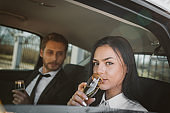 Business people drink champagne in a car after a long business trip