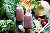 Freshly blended fruit smoothie in glass jar with straw