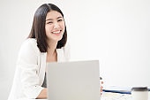 Young asian woman employee smiling with happiness and confident while looking toward camera with a white meeting room background, concept happy working environment.