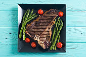 Grilled T-bone steak with asparagus and cherry tomatoes