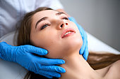 Beautician hands in gloves touching face of attractive woman. Facial Beauty. Beautiful young female with soft smooth healthy skin. Plastic Surgery Concept. Masseur doing relax facial massage at spa