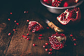 Pomegranate pieces on rustic wooden surface