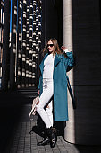 Young beautiful stylish woman walking in blue coat, white jeans and black shoes, holding pink bag in hands, street style, spring summer trend. Fashion season shopping concept