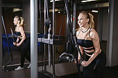 Young fitness woman doing workout exercise with exercise-machine on triceps in gym. Bodybuilding healthy lifestyle muscular concept