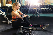 Relaxing after training. Beautiful young woman sitting at gym and having a brake after exercize. Young female at gym taking a break from workout. Sports fitness model. Healthy lifestyle concept