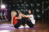 Female trainer teaching woman making abdominal exercises. Making training together. Sporty healthy lifestyle concept