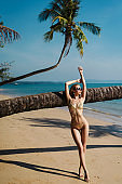 Pretty woman in sexy golden swimsuit and sunglasses posing at the beach and palm tree background
