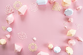 A variety of faceted gemstones, made of paper on a pink background.