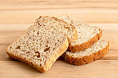 Three slices of whole wheat toast bread isolated on light wood.