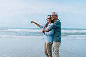 Asian couple senior elder retire resting relax at beach honeymoon family together happiness people lifestyle