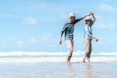 Asian couple senior elder retire resting relax dancing at sunset beach honeymoon family together happiness people lifestyle