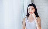 Portrait of Young Beautiful Asian woman clear face skincare her happy and smile at white room,Copy space.