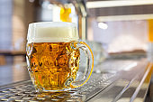 Freshly poured draft lager beer in a dimpled glass mug on stainless steel counter in a modern pub. Space for text.