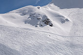 Mountain skiers and snowboarders riding from the mountain at sunny winter day. A lot of tracks from skis and snowboards outside the track. Freeride.