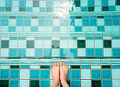 Selfie of feet and legs in green swimming pool and waves background or texture. Top view. Beautiful young female barefoot under aqua water on summer holiday.