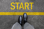 Business man standing on street background with word new start written. Pair of feet and black shoes on tarmac road with yellow race line beginning idea concept. Top view. Businessman of starting.