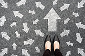 Feet and arrows on road background from above. Businesswoman standing on pathway with drawn white many direction arrows choice. Top view of A businesswoman black shoes. Motivation and growth concept.