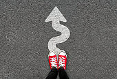Feet and white arrow sign go straight on road background. Top view of woman. Forward movement and motivation idea concept.