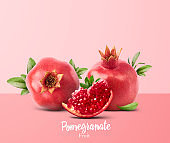 Fresh ripe pomegranate with green leaves isolated on white background.