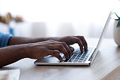 Close-up of african businessman typing on his computer at his office