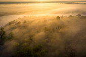Sunrise over foggy riverbank. Fog on river aerial view. Misty river in sunlight from above