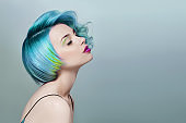 Portrait of a woman with bright colored flying hair, all shades of blue purple. Hair coloring, beautiful lips and makeup. Hair fluttering in the wind. Sexy girl with short  hair. Professional coloring