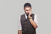 Portrait of sad alone depressed handsome bearded brunette man in white shirt and waistcoat standing, holding head down, touching eyes and crying.