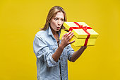 Holiday surprise. Portrait of astonished curious woman in denim shirt looking inside gift box. studio shot isolated on yellow background