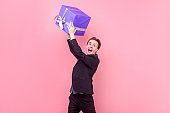 Portrait of overwhelmed happy man in suit and with stylish haircut screaming for joy. studio shot isolated on pink background