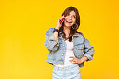 Portrait of happy excited beautiful brunette young woman in denim casual style standing, hand on waist, looking away and talking on her mobile phone.