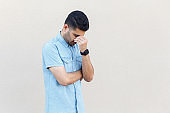 Problem, depression or sickness. Portrait of sad alone handsome young bearded man in blue shirt standing, holding head down and crying.