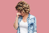 Portrait of sad alone depressed young woman with curly hairstyle in casual blue shirt standing and holding head down and crying.