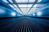 blurred motion of airport moving walkway, blue toned