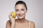 Portrait of charming beautiful healthy caucasian middle aged woman holding green apple, she love to eat fruit, make her get good health, nice skin, lose weight and weight control.