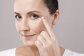 Middle aged woman with perfect face skin applying cosmetic cream with finger on skin near eyes and looking at camera isolated on grey background.