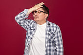 trouble, difficulties or bankruptcy concept. Portrait of sad alone businessman in checkered shirt and eyeglasses standing, touching his forehead.
