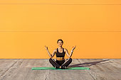 Young sporty attractive woman practicing yoga, doing ardha padmasana exercise, meditating in half lotus pose with mudra gesture