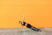 Young sporty attractive woman practicing yoga, doing vasisthasana exercise, side plank pose,