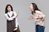 Portrait of young girl looking at camera and showing stop or ignore to another girl who screaming at her. conflict between two friend or partners.