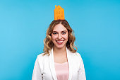 Home insurance. Portrait of positive woman standing with small paper house on her head and smiling broadly. blue background