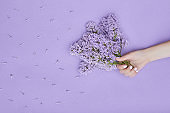 Beauty Hand of a woman with blue flowers lies on table, blue paper background. Natural cosmetics product and hand care, moisturizing and wrinkle reduction, skincare