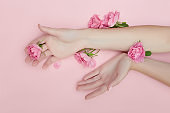 Beauty Hand of a woman with red flowers lies on table, pink paper background. Natural cosmetics product and hand care, moisturizing and wrinkle reduction, skincare