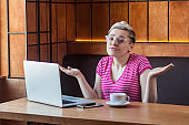 Not sure! Confused young girl freelancer with blonde short hair, in pink t-shirt and eyeglasses is sitting in cafe and working on laptop with raised arms and puzzled face,