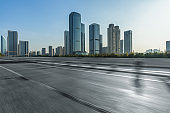 Clean asphalt road with city skyline background