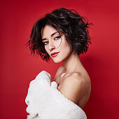 Sexy woman with short hair cut in white sweater on red background. Perfect girl with wet tousled dark hair and bright makeup, short hair, beauty and hair care. Naked shoulder women