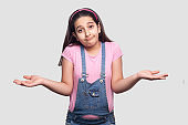 I don't know. Portrait of confused brunette young girl in casual style, pink t-shirt and blue overalls standing, raised arms and looking at camera.